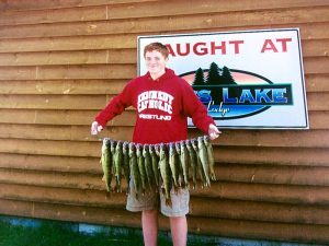 A fantastic stringer of fish, being held by a young man in a red sweatshirt in front of Cass Lake Lodge.