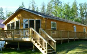 The Beautiful Loon cabin at Cass Lake Lodge can comfortably sleep 9 people! It has a light wood exterior with a gorgeous full deck.